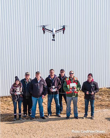 Seven people lined in with for a photo at a farm - most holding a drone controller - with a drone in the flying in the foreground