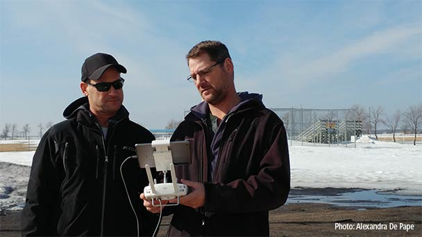 Two men looking at the screen of a tablet attached to a drone controller.